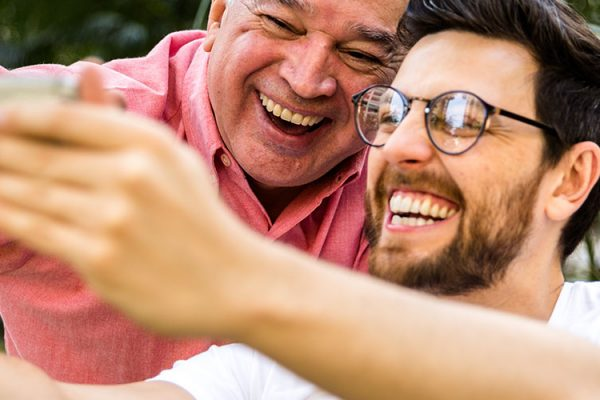 A younger man taking a selfie with an older man.